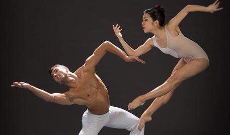 Two dancers in white - male on the left gesturing to the left and female on the right in mid jump.