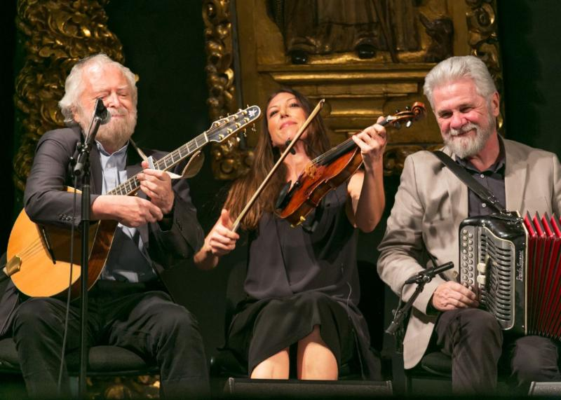 Three musicians perform - all are seated. Left to right_ a man with a beard plays the mandolin_ a woman with long brown hair and a black dress plays the fiddle_ and a nother man with a beard plays the accordion.