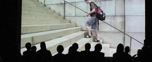 Screen shot of DEEj walking up the stairs at college with silhouette of audience in front of screen.