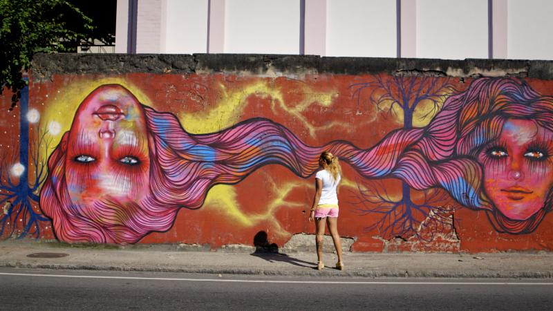 O woman in a white shirt and pink sort stands facing a mural of two women_s heads on a large brick red wall.