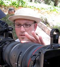 Filmmaker Jonathan Gruber adjusting a film camera.