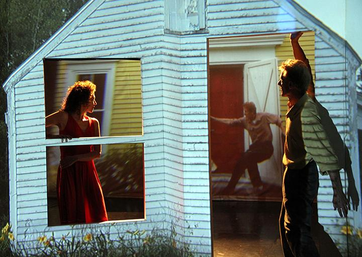 Image of a small white clapboard house.  A female dancer on the left in the window. A male dancer on the right by the door.