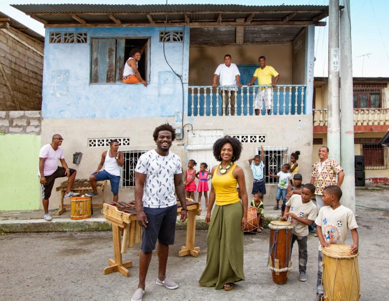 Musical Group Rio Mira stands in front of a two story pale blue and white house.