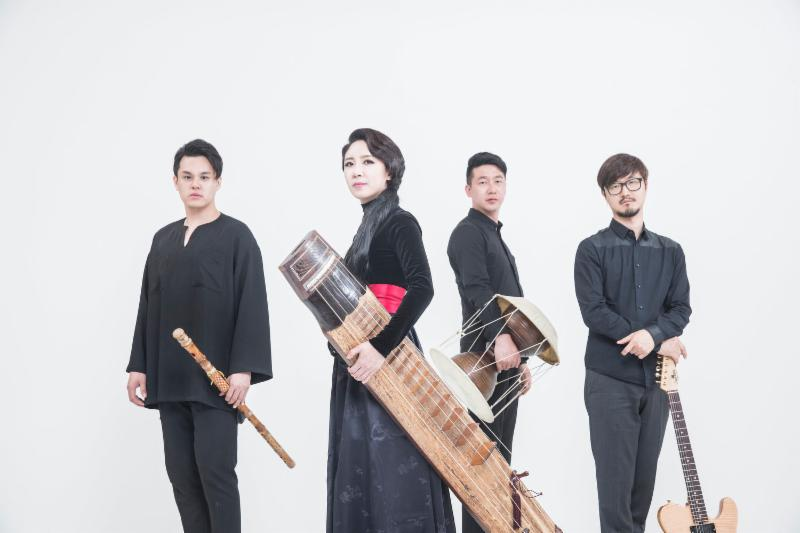 Four Korean musican stand dressed in black in front of a white backdrop.  They hold traditional instruments.