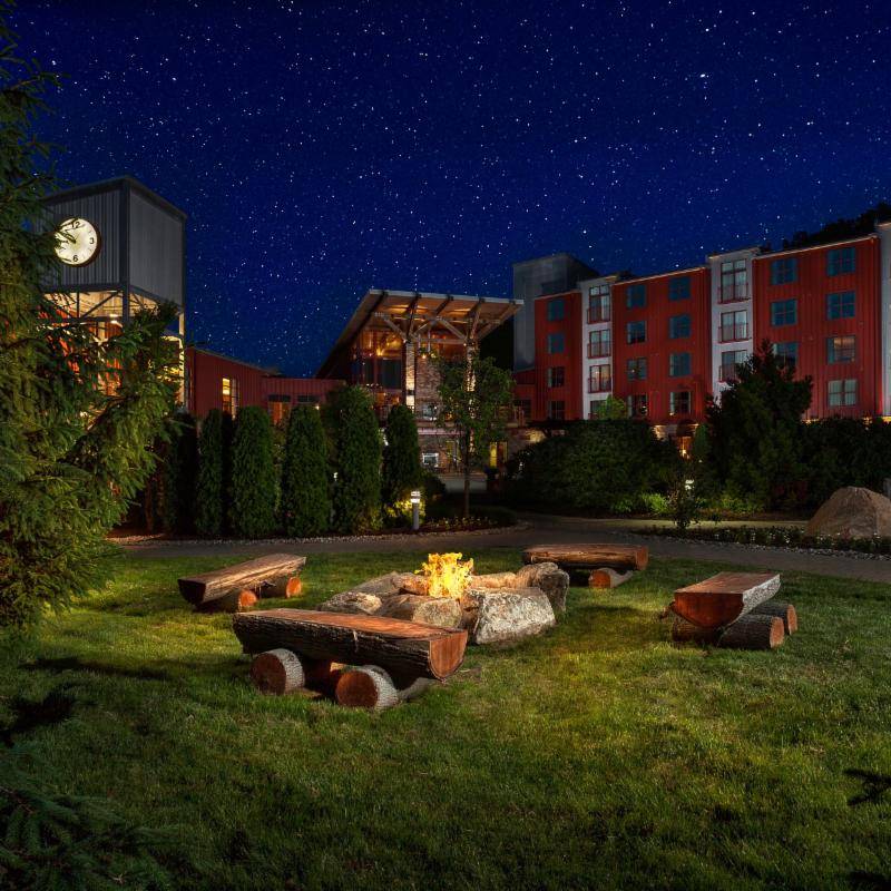 Firepit in foreground with hotel buildings encircling. Dark blue night sky with stars.