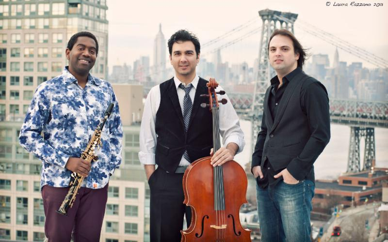 Three musicians stand on a rooftop against a view of the NYC skyline.