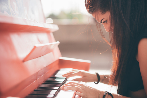 Close up of a young beautiful reddish brown hair caucasian girl playing piano - creative_ performance_ music concept - she is dressed with a black shirt and plays a red piano