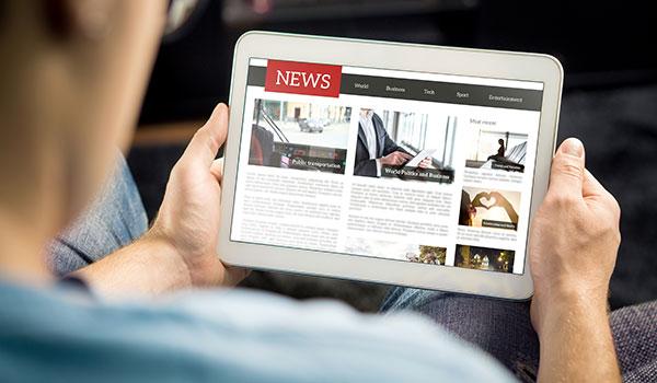 Man reading news headlines on tablet
