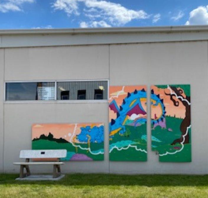 Mural in 3 separate panels of a blue dragon outside on grass. The dragon is in a thought bubble so it looks like anyone sitting on the bench is thinking it.