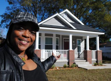 Woman standing in front of new house