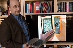 Professor Vladimir Bulović discusses transparent solar cells being commercialized by MIT spinoff Ubiquitous Energy, based in Menlo Park, Calif. The cells can power an electronic book reader, as seen in video behind him. Photo, Denis Paiste.