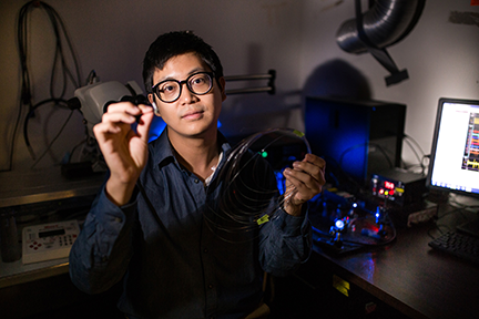 Graduate student Seongjun Park holds an example of a new flexible fiber, which is no bigger than a human hair and has successfully delivered a combination of optical, electrical, and chemical signals back and forth into the brain. Photo, Young Gyu Yoon