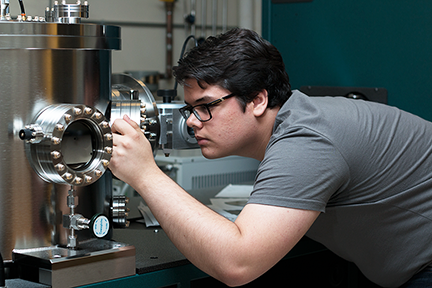 MPC-CMSE Summer Scholar Grant Smith looks into a sputter deposition chamber where he makes ultra thin films _from 2 to 10 nanometers thick_ of special magnetic materials suitable for spin-based electronics. He is working under MIT Assistant Professor of El