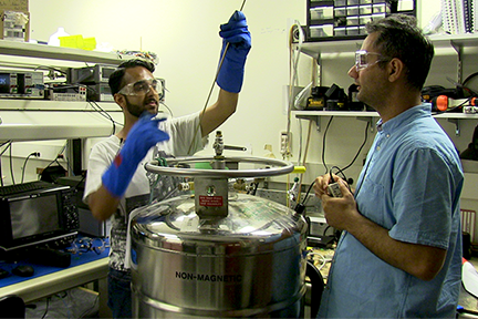 Summer Scholar Saleem Iqbal checks the level in a dewar_ a special canister of liquid helium_ with MIT Postdoctoral Associate Reza Baghdadi. Iqbal tested a sample of a new superconducting memory cell at temperatures of 4.2 kelvins.