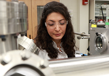 MIT electrical engineering graduate student Farnaz Niroui works at a thermal evaporator which she uses to deposit a gold coating on squeezable switches, or