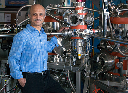 MIT Senior Research Scientist Dr. Jagadeesh S. Moodera stands in front of a custom-built cluster molecular beam epitaxy _MBE_ system used to fabricate ultra thin films. He studies  devices that exhibit resistance-free_ spin-polarized current.