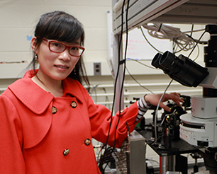 MIT Physics graduate student Qiong Ma is doing original research on the electrical properties of grapheme-based devices using laser light stimulation. Photo, Denis Paiste