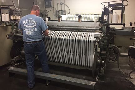 Marty Ellis, of Inman Mills in South Carolina, checks a machine manufacturing fabric developed through AFFOA. Credits Courtesy of the AFFOA