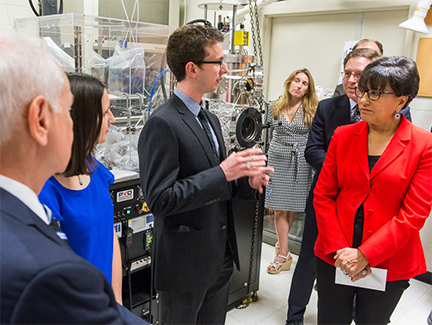 U.S. Secretary of Commerce Penny Pritzker, right, listens to Materials Science and Engineering graduate student Derek M. Kita, center, during a Sept. 18, 2015, visit to MIT's Thin Film Deposition Lab. Materials Science Professors Lionel C. Kimerling, far left, and Krystyn J. Van Vliet, center back, are conducting research at MIT as part of the Commerce Dept.-funded American Institute for Manufacturing Integrated Photonics (AIM Photonics). Photo, Justin Knight.