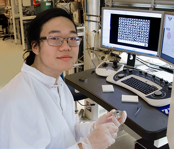 Summer Scholar Justin Cheng holds an experimental sample of nanostructured gold on silicon that has potential for use in sensors, catalysts and display technologies based on selective light absorption.