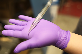 Graduate student Chong Hou holds a leftover silica preform after it has been used. The tapering tip shows how the preform is stretched to make long strands of fiber while in the furnace. Photo, Jose-Luis Olivares, MIT.
