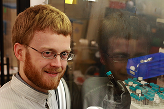 MIT physics graduate student Patrick R. Brown holds a vial of lead sulfide quantum dots inside a glovebox in the Organic and Nanostructured Electronics (ONE) Lab  at MIT. Brown is working to understand how the surface chemistry and electronic properties of quantum dots can be tuned to increase the efficiency of quantum dot solar cells. Photo, Denis Paiste, Materials Processing Center.