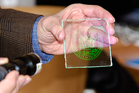 Professor Vladimir Bulović demonstrates how the MIT logo appears when an LED light shines on glass coated with thin layers of quantum dots that were inkjet printed. Photo, Maria E. Aglietti.