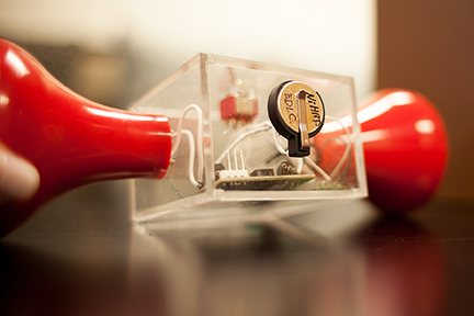 To demonstrate the supercapacitor's ability to store power, the researchers modified an off-the-shelf hand-crank flashlight (the red parts at each side) and installing a small supercapacitor in the center. Photo, Melanie Gonick, MIT News