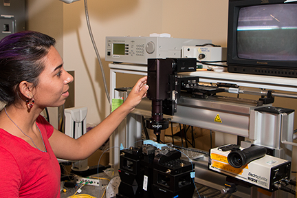 Summer Scholar Ashley Del Valle Morales learns how to operate a laser and detector system she will use during her summer project under Senior Research Scientist Dr. Anuradha Agarwal.