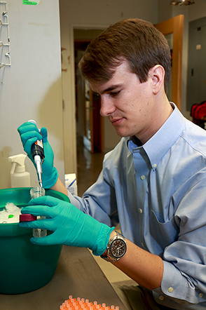 MIT Physics graduate student James Owen Andrews works at a bench in the Cissé  lab. Andrews is studying genetic transcription processes with single molecule resolution. Photo, Denis Paiste, Materials Processing Center
