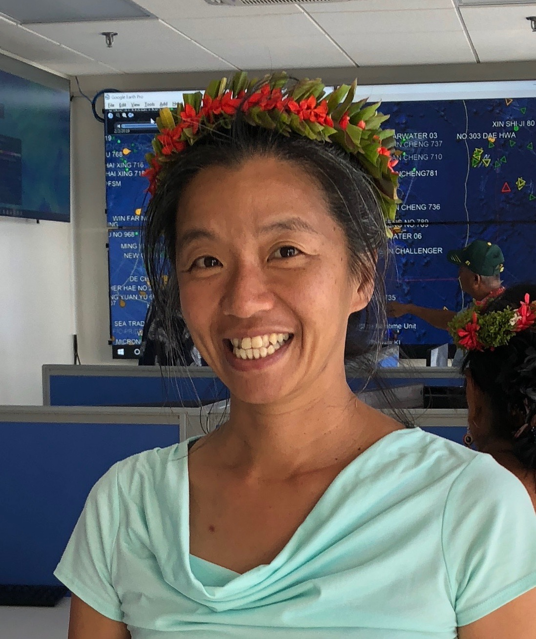 Head shot of  Ming Wei wearing a flower lei.