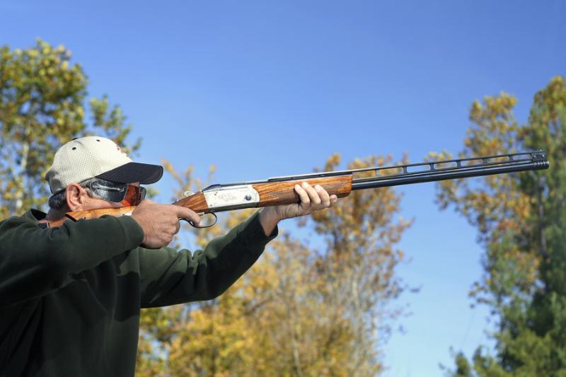 Man shooting a shotgun. Bird hunting or shooting skeet.