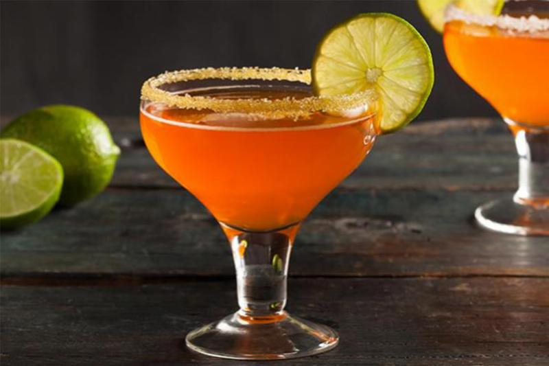 A candy corn margarita with fruit wedge.