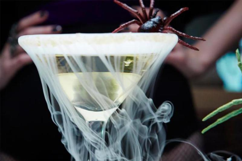 A Halloweenie-Tini in a cocktail glass with fog and accompanying spider.