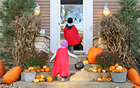 Two kids wearing capes trick-or-treating on Halloween on a front porch decorated with pumpkins.