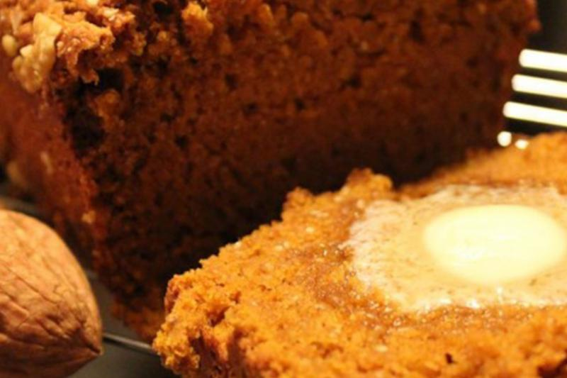 A closeup of butter melting on a slice of warm pumpkin bread.