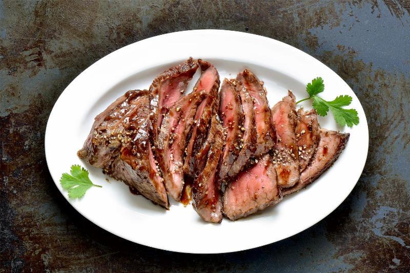 A plate with a sliced flank steak.