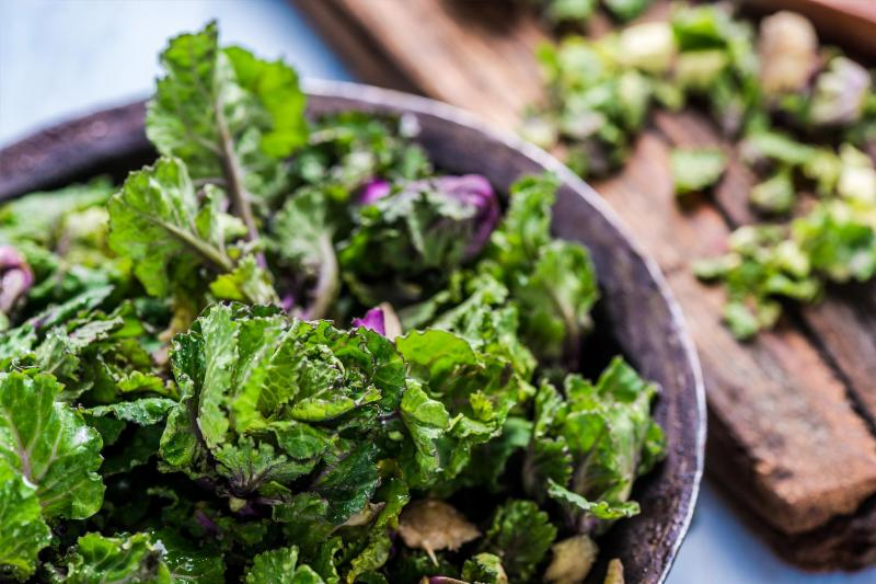 A shaved brussels sprout and kale salad with pecans in a bowl.
