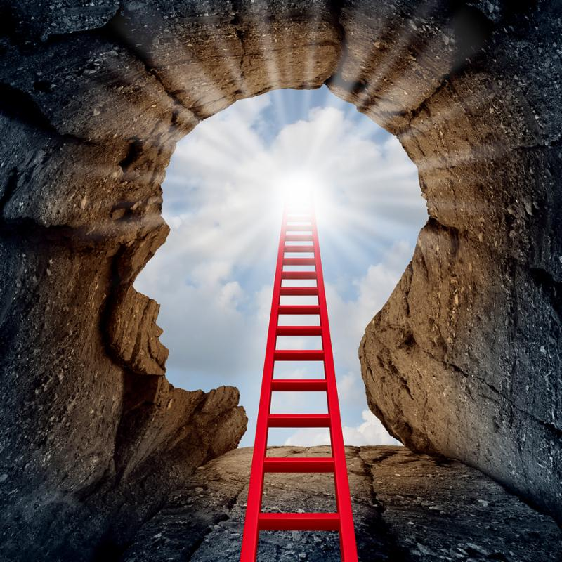 Concept of open mind as a a deep mountain cliff shaped as a human head with a ladder leading to the outside towards a glowing sun as a psychology and mental health metaphor for spiritual discovery.