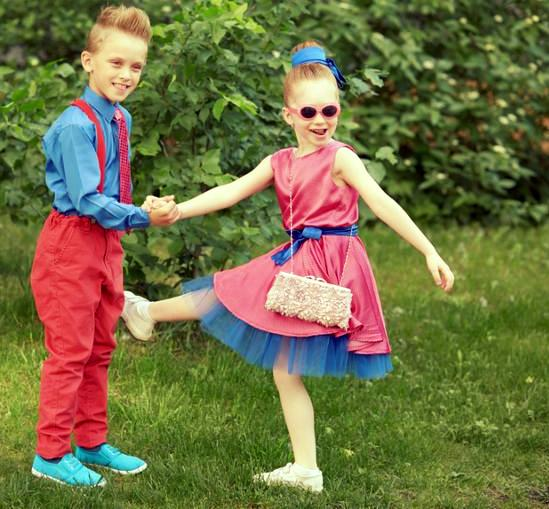 Boy and girl dressed in red and blue costumes dance at grassy lawn