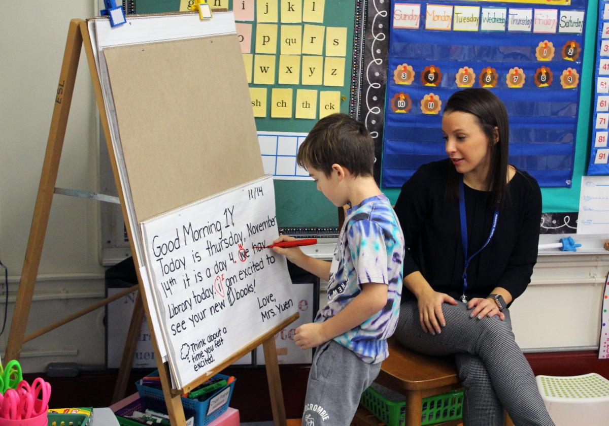 A student uses a marker to edit a note written on an easel as his teacher looks on.