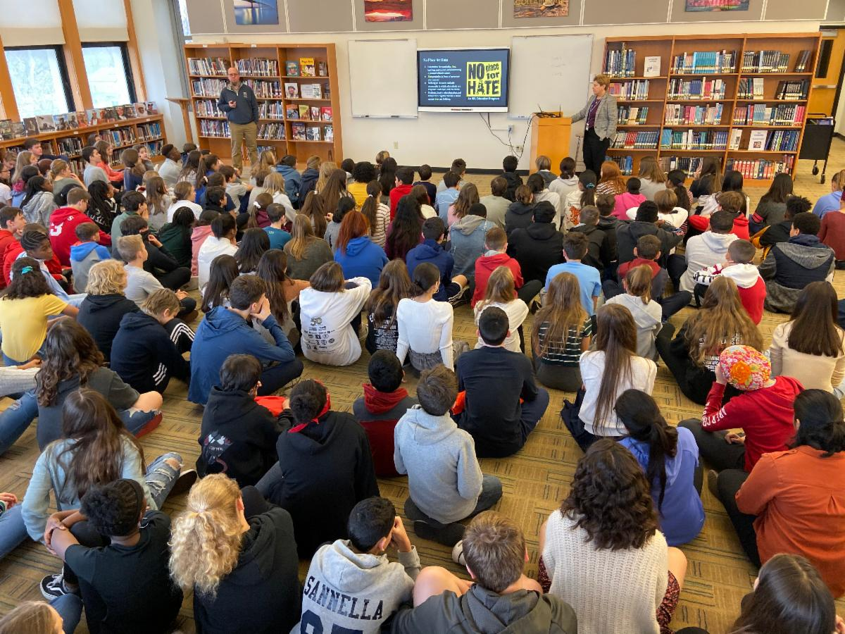 Pelham Middle School students sit in the library as Principal Sabia leads an assembly.