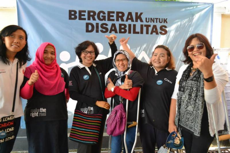 Representatives from DRF Indonesia grantees stand in front of a banner