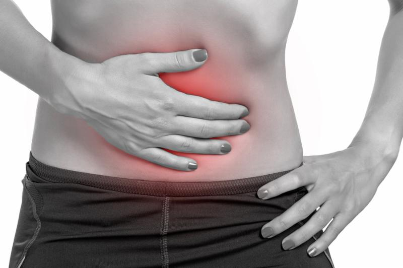 Woman suffering from stomach pain isolated in white.