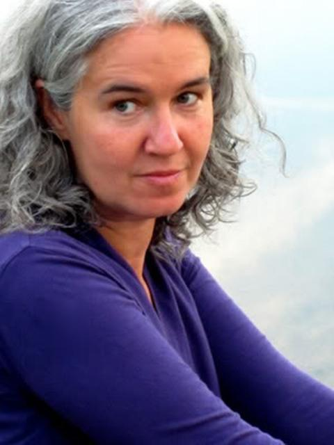 Image of Melissa Tuckey. wearing a long sleeve purple shirt. She has a serious yet kind expression_ wears her gray hair tucked behind her ears.
