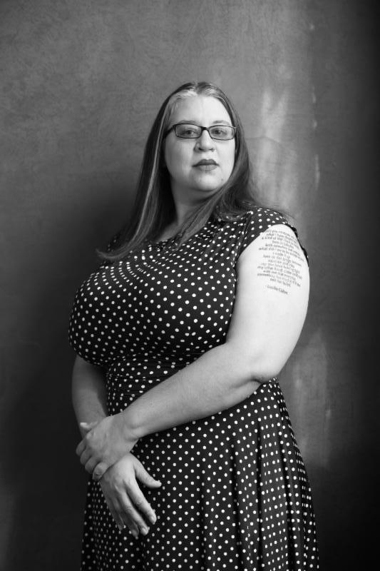 Black and white Image of Tara Betts. She wears a black and white polka dot dress and looks toward the camera with a neutral expression.