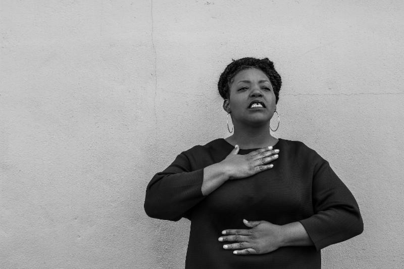 Black and white image of Mahogany L Browne. Her head is tilted slightly back and she appears to be ready to say something. Her right palm is on her chest and her left palm is on her belly. She wears a black long sleeved blouse and hoop earrings.