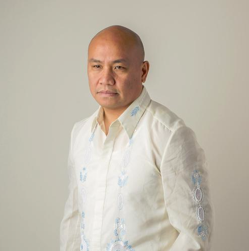 Photo of Patrick Rosal_ a bald asian man with a neutral expression standing looking off into the distance.  He wears a beige long sleeved button up shirt with light blue and white embroidery.