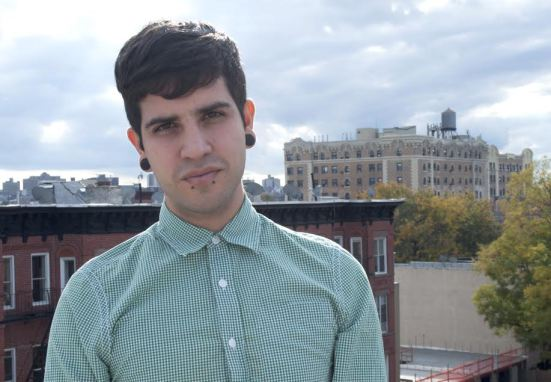 Image of Christopher Soto in  green stripped shirted standing in front of a city scape.
