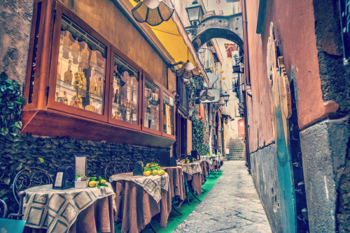 Rustic tables in a narrow alley in world famous Sorrento. Campania_ Italy